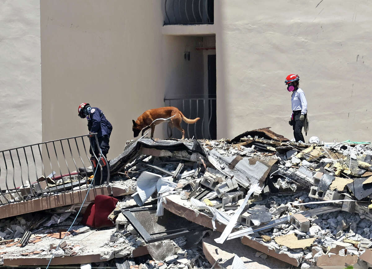 Search and rescue personnel search for survivors through the rubble with their dogs at the Champlain Towers South in Surfside, Fla., Sunday, June 27, 2021. The apartment building partially collapsed on Thursday, June 24. (David Santiago/Miami Herald via AP)