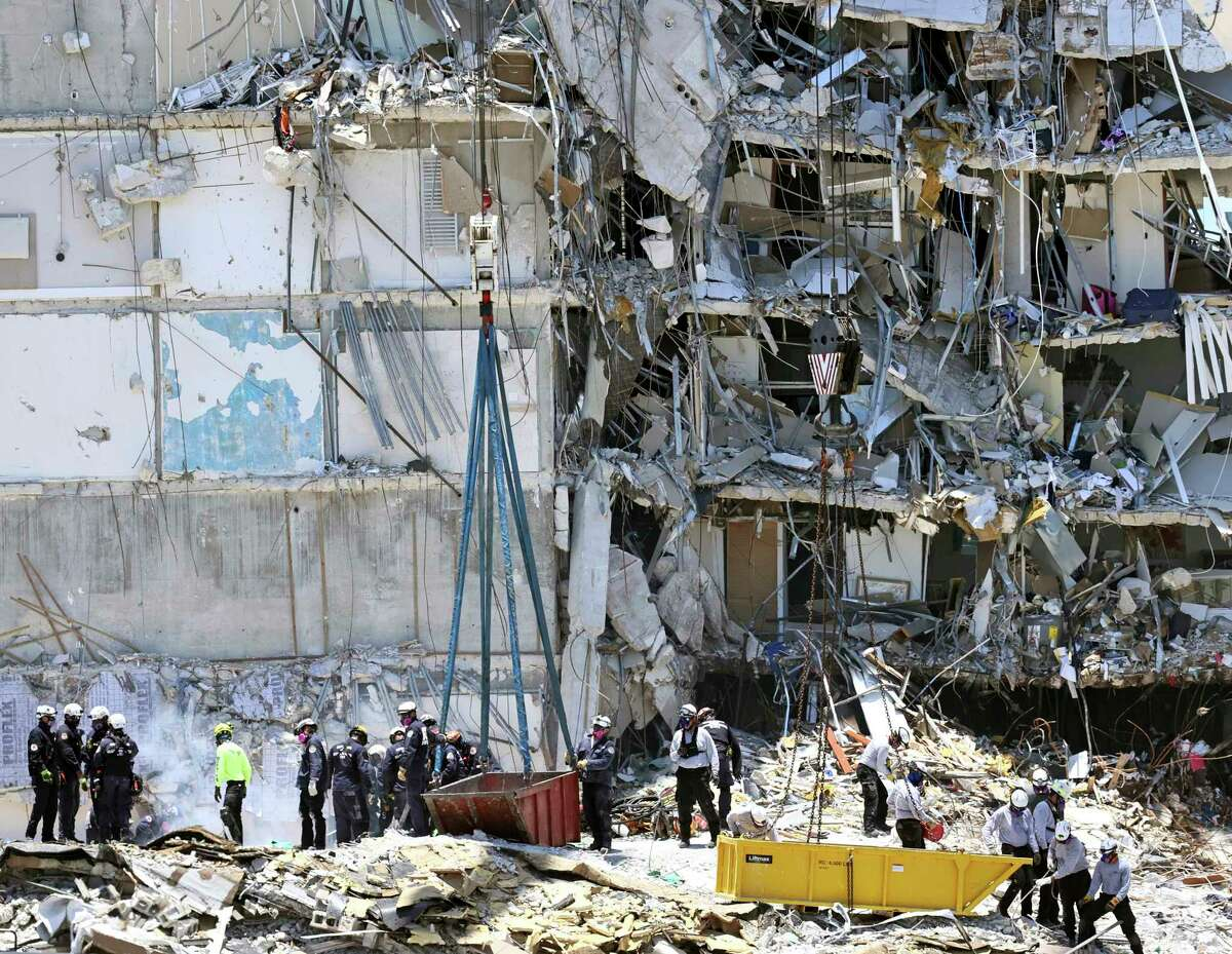 Search and rescue personnel search for survivors through the rubble at the Champlain Towers South in Surfside, Florida, Sunday, June 27, 2021. The apartment building partially collapsed on Thursday, June 24. (David Santiago/Miami Herald via AP)