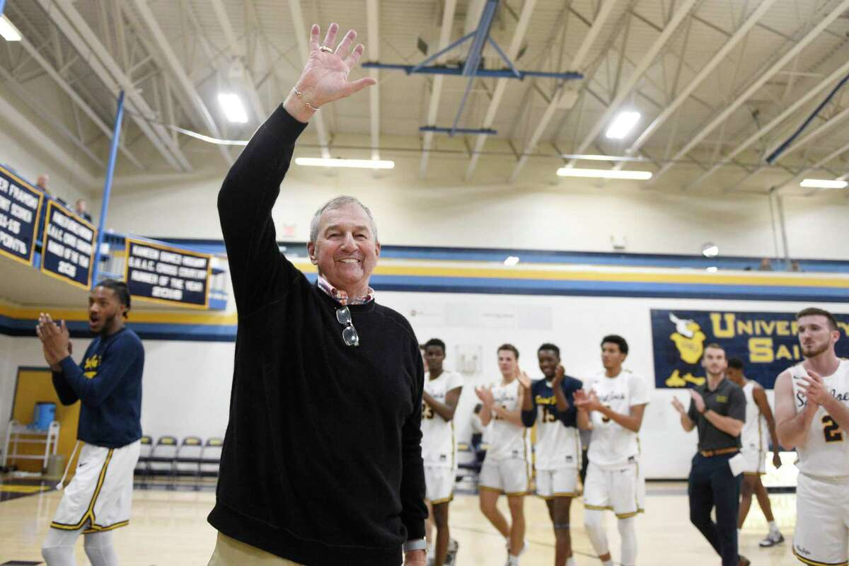 Saint Joseph coach Jim Calhoun smiles and waves to fans after the team's win in an NCAA college basketball game Friday, Jan. 10, 2020, in West Hartford, Conn. Now coaching Division III basketball with the same fire he stalked the sidelines at UConn, Calhoun reached his 900th win as a college coach. (AP Photo/Jessica Hill)
