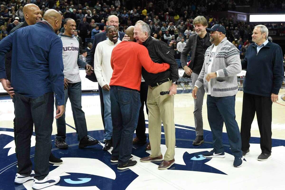 Former Connecticut head coach Jim Calhoun, center right, hugs former player John Gwynn during a halftime ceremony honoring the 1989-90 UConn men's team during an NCAA college basketball game against Cincinnati, Sunday, Feb. 9, 2020, in Storrs, Conn. (AP Photo/Jessica Hill)