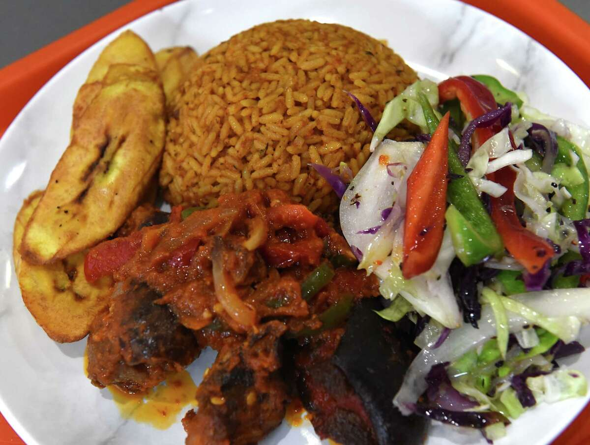 Jollof rice, tomato-based rice mixed with onions and served with a side of fried plantains, veggies and a choice of chicken, beef, fish, goat meat or pork, is on the menu at Keobi in Albany.(Lori Van Buren/Times Union)