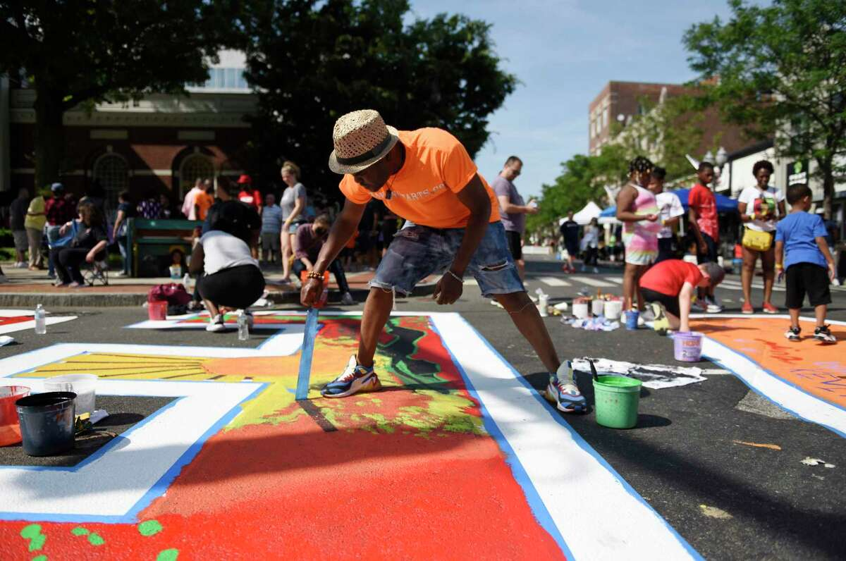 Artist Jean Benoit, a Stamford native, participates in the Black Lives Matter mural restoration at Juneteenth celebration in Stamford on Sunday. More photos inside on page A12