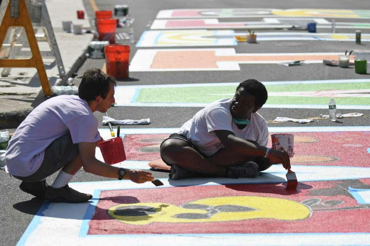 Marc DiMartino, left, and artist Chaz Daviscz participate in the Black Lives Matter mural restoration at the Juneteenth celebration.