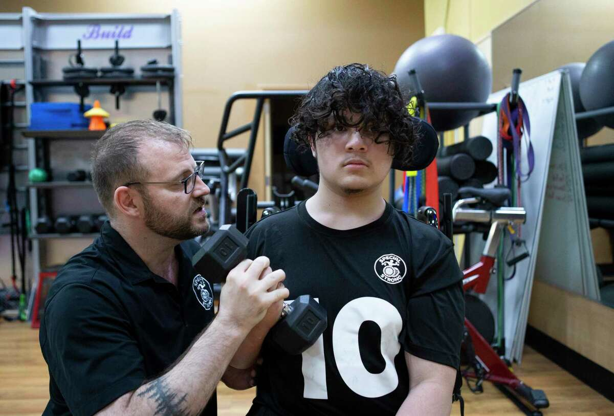 Henry Bellard, 17, who uses a wheelchair because of brain trauma, warms up with Mike Lutey, owner and trainer of Special Strong, before his workout session with Lutey Thursday, June 17, 2021, at Anytime Fitness in League City. Special Strong, an adaptive and inclusive fitness training program, has opened a franchise for Southeast Texas for youths and adults with mental and/or physical disabilities.