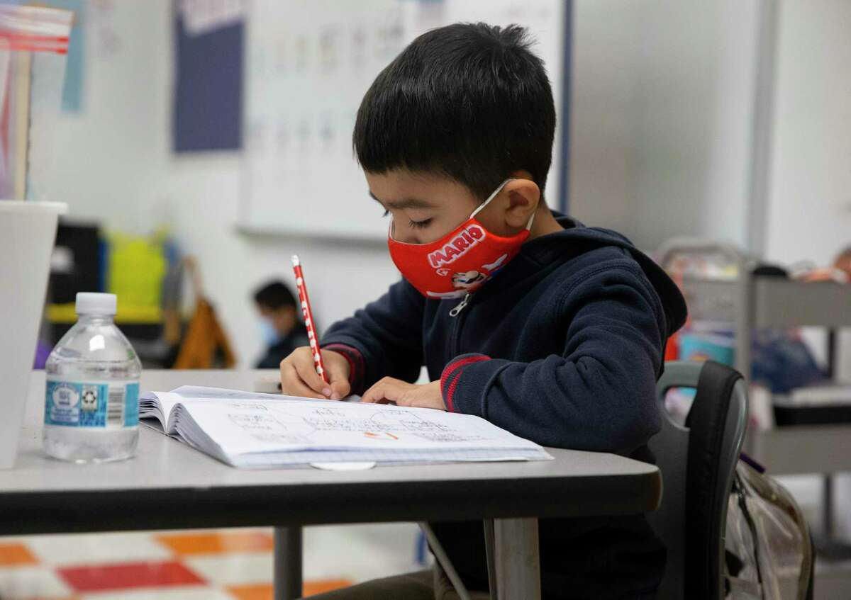 """James DeAnda Elementary School student Kayden Garza-Munoz working on classwork Tuesday, Feb. 9, 2021, in Houston. Children at Risk's annual rankings labeled them as """"pandemic"""" proof for earning A and B accountability ratings for three years in a row while also serving high rates of economically disadvantaged students."""