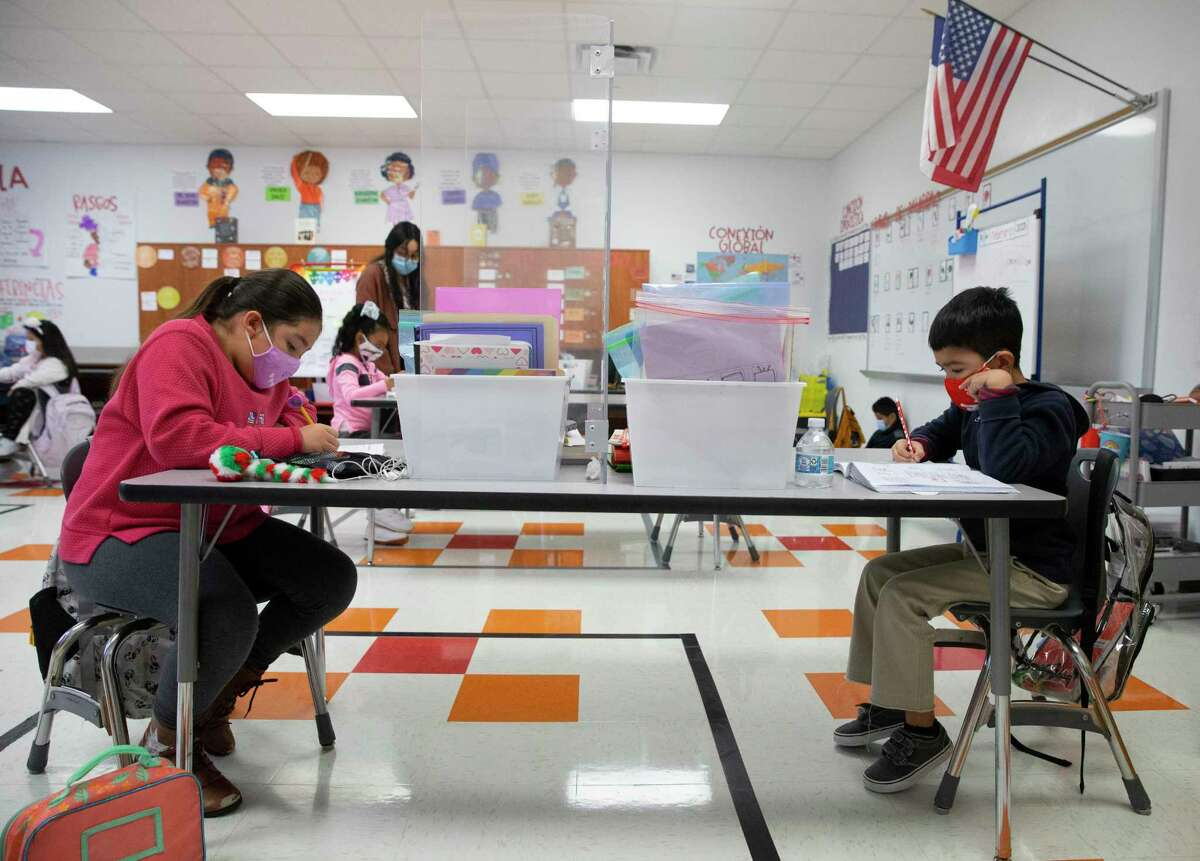 """James DeAnda Elementary School students Perla Villegas, left, and Kayden Garza-Munoz working on classwork Tuesday, Feb. 9, 2021, in Houston. Children at Risk's annual rankings labeled them as """"pandemic"""" proof for earning A and B accountability ratings for three years in a row while also serving high rates of economically disadvantaged students."""