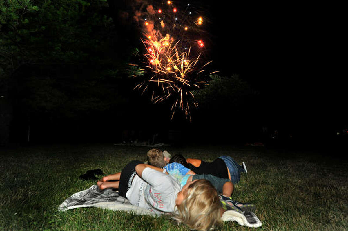 In this 2020 file photo, citizens lay on a blanket as they watch the fireworks at Edwardsville High School.