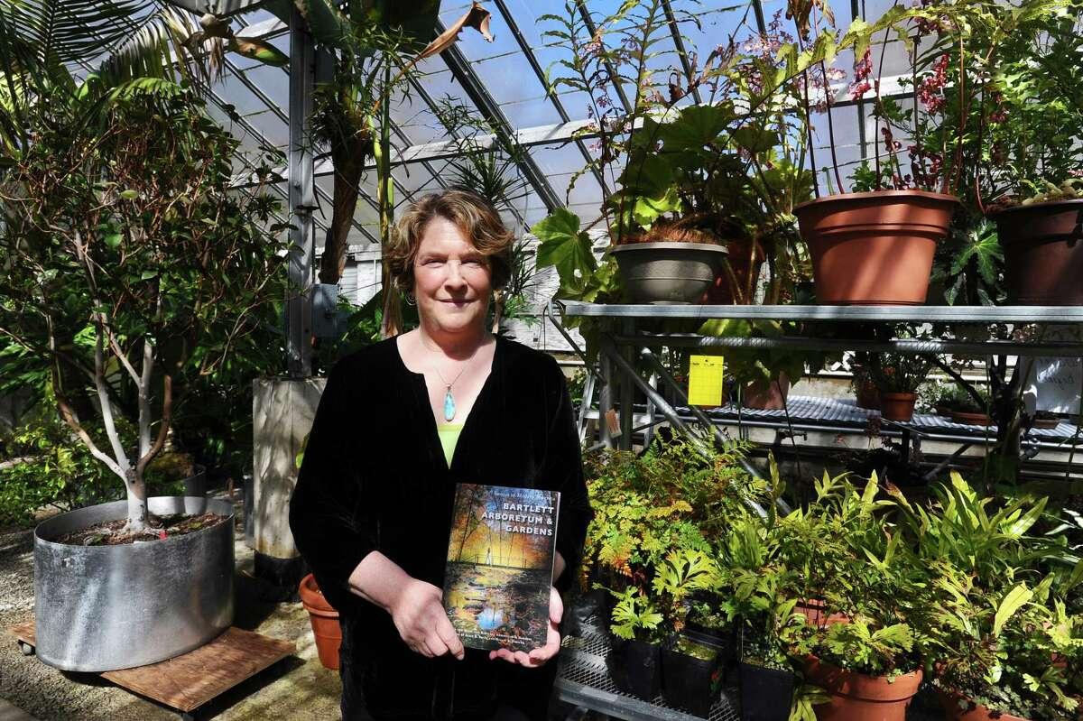 """Bartlett Arboretum & Gardens CEO S. Jane von Trapp poses with her book """"Bartlett Arboretum & Gardens"""" inside the greenhouse at the Bartlett Arboretum & Gardens in Stamford on March 29, 2017. Von Trapp's last day as CEO is June 30, 2021."""
