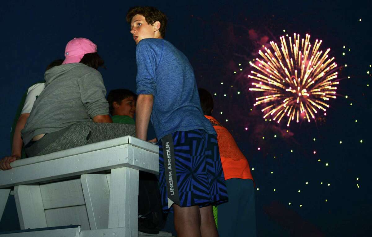 Locals including Ryan Lovas and his friends gather for the annual fireworks show at Calf Pasture Beach in Norwalk, Conn.