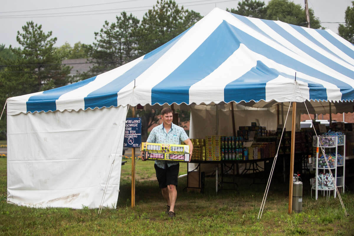 Quincy Crawford of Farwell purchases fireworks Friday, June 25, 2021 at a tent run by Brian Cassaday of Gladwin and his mom, Donna, located next to the Shell station on Eastman Avenue and W. Wackerly Street in Midland. (Katy Kildee/kkildee@mdn.net)
