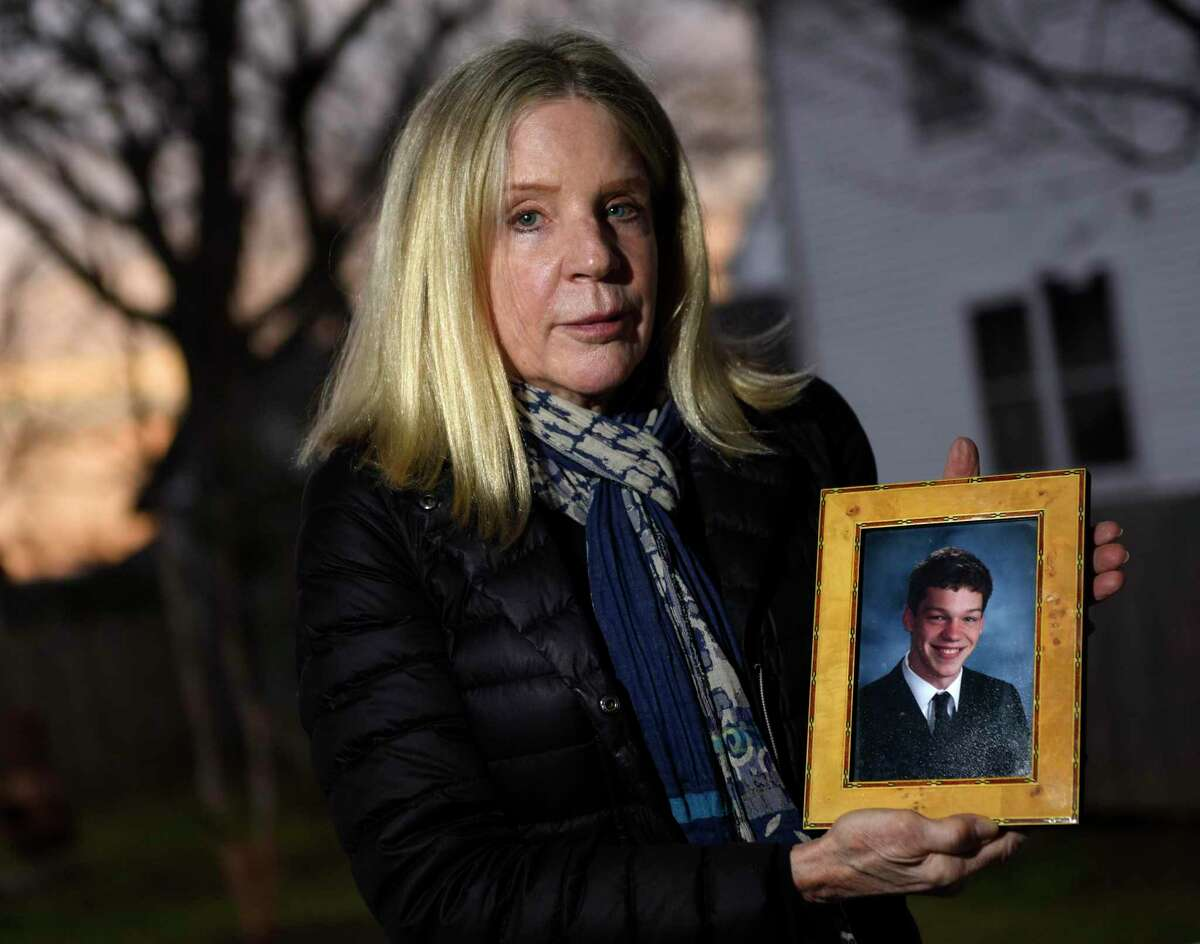Dede Yoder poses with a photo of her son, Chris, outside her home in Norwalk, Conn., on Wednesday, Nov. 25, 2020. Chris died in 2017, at age 21, of an overdose of fentanyl and carfentanil. Yoder said that he was prescribed OxyContin when he was a teenager, and she believes his OxyContin use led to him later becoming addicted to heroin.