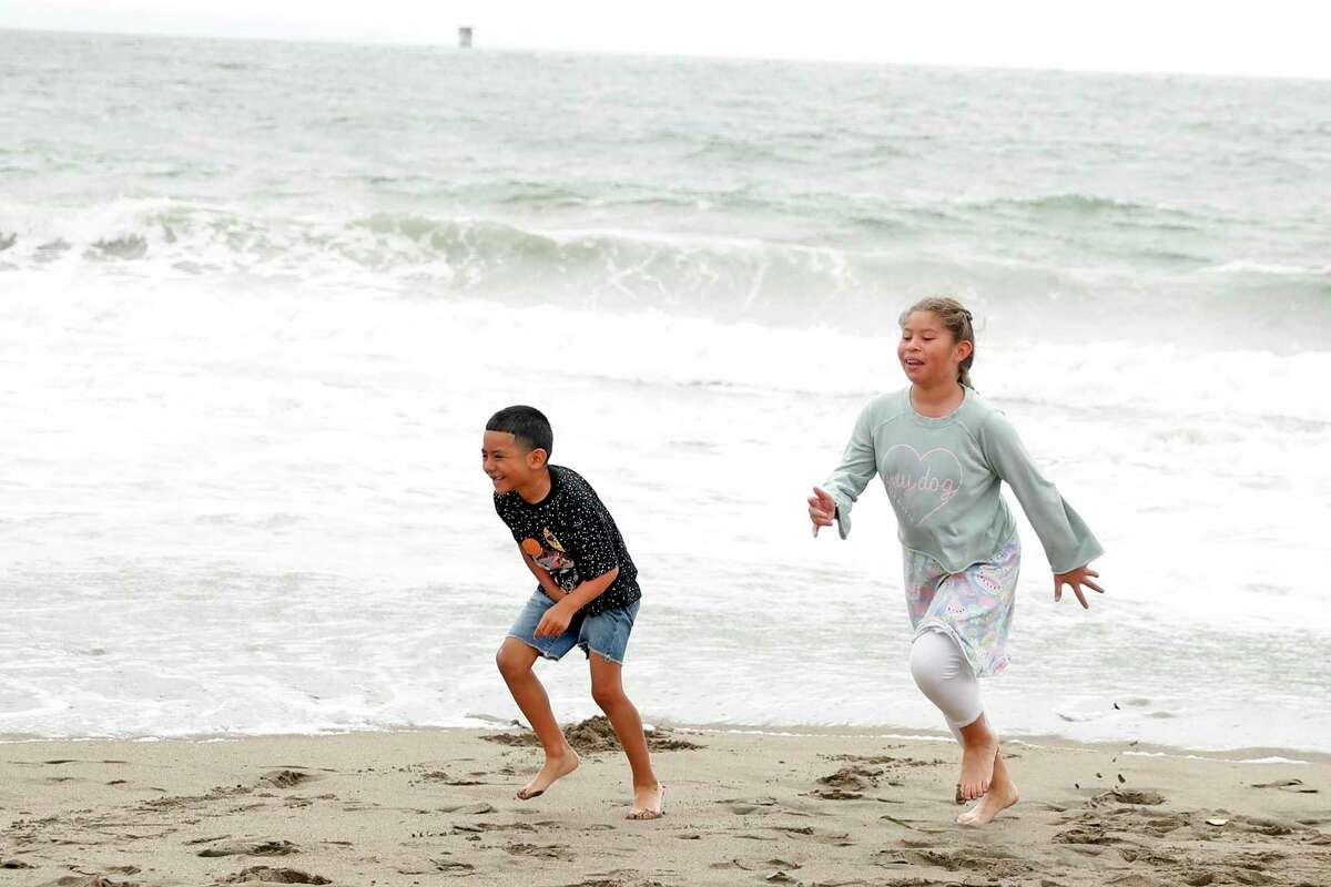 Kaydin Gonzalez, 7, and his sister, Josie, 10, run from the surf at Baker Beach in San Francisco, Calif. The Bay Area was largely spared from the heat wave baking the Pacific Northwest. Portland, Seattle and parts of Northern California have broken heat records, but the Bay Area has largely avoid the brunt of the latest heatwave.