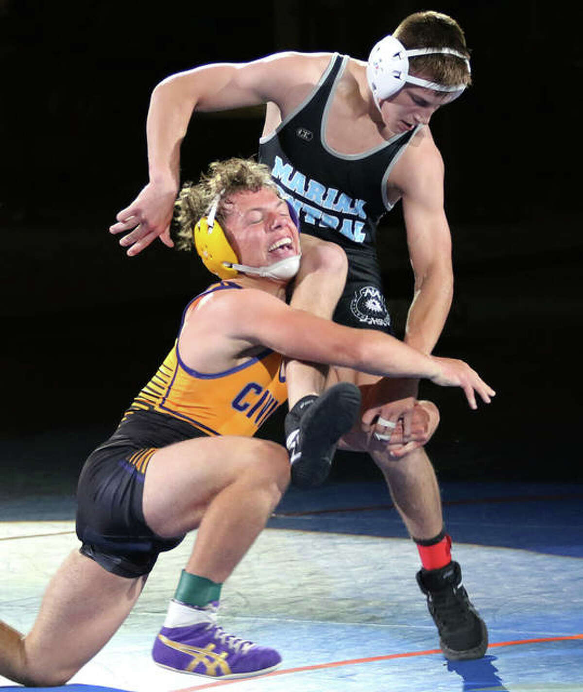 CM's Caleb Tyus (left) shoots in for a takedown against Woodstock Marian Central Catholic's Chris Moore late in Tyus' 7-2 win in the 138-pound title match Friday in the IWCOA Class 2A state meet in Springfield.