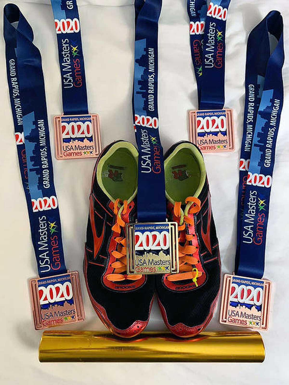 Some of the medals, as well as shoes and relay baton, from Mike Young's Saturday performances at the USA Masters Games in Grand Rapids, Mich.