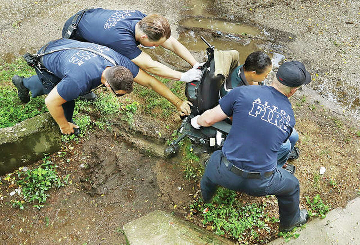 It was helping hands to the rescue Monday after a woman in a motorized wheelchair got stuck in the mud in the 700 block of Alby Street. A brief but heavy morning downpour soaked the area, but Alton firefighters were able to free the wheelchair with a little elbow greese.