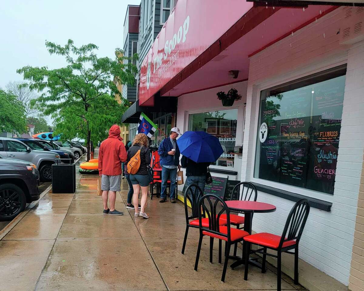 Despite the rain, visitors still stood outside The Scoop to enjoy some ice cream. (Colin Merry/Record Patriot)