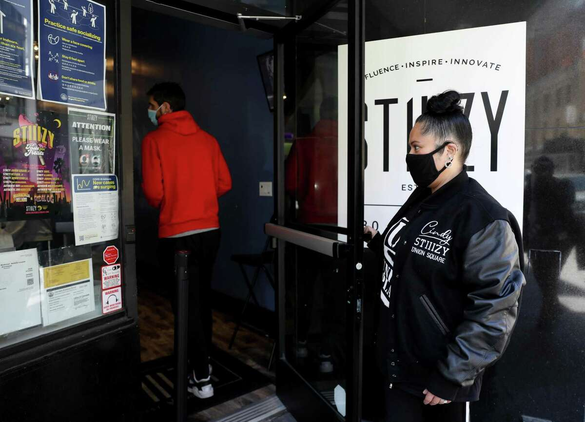 Cindy De La Vega, the first Latina dispensary owner in San Francisco, opens the door for a customer at her store, STIIIZY Union Square in San Francisco, Calif. At a time when so many other businesses were closing down, cannabis in San Francisco has seen an enormous boom. Permits for dispensaries were off the chart during the last year, and at least 10 storefronts have opened in the last year, even though cannabis as a whole got zero small business aid during the pandemic.