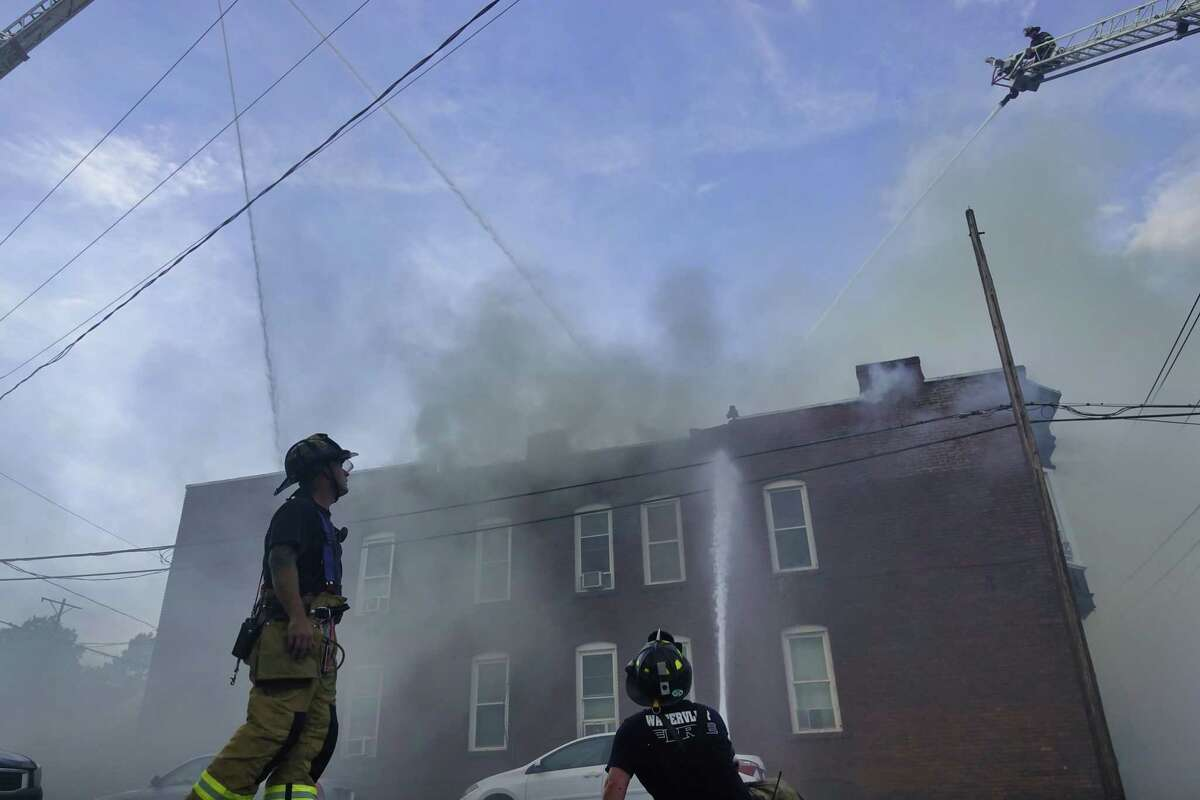 Firefighters battle a fire in three row houses near the intersection of 24th Street and Broadway on Monday, June 28, 2021, in Watervliet, N.Y. The fire tore through three row houses. (Paul Buckowski/Times Union)