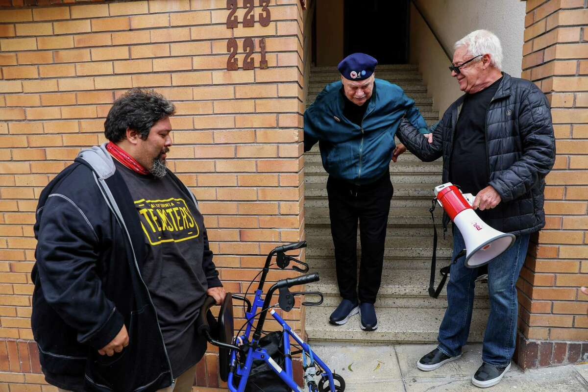Ruben Bustillos, Teamsters Local 70, Oakland, left, holds Allan Baird's walker as Baird is aided by his friend Cleve Jones, right, down the stairs after Jones led a march from Harvey Milk Plaza to Baird's home in San Francisco.