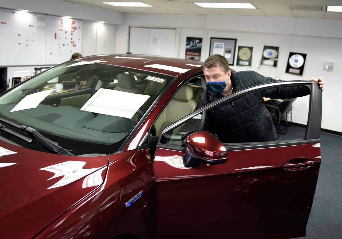 Senior Sales Representative Elvis Kocan shows a plug-in hybrid electric Honda Clarity at the Greenwich Honda dealership in Greenwich, Conn., on Feb. 9, 2021. Connecticut announced on June 28, 2021 the expansion of its subsidies program for electric vehicles including plug-in hybrids.