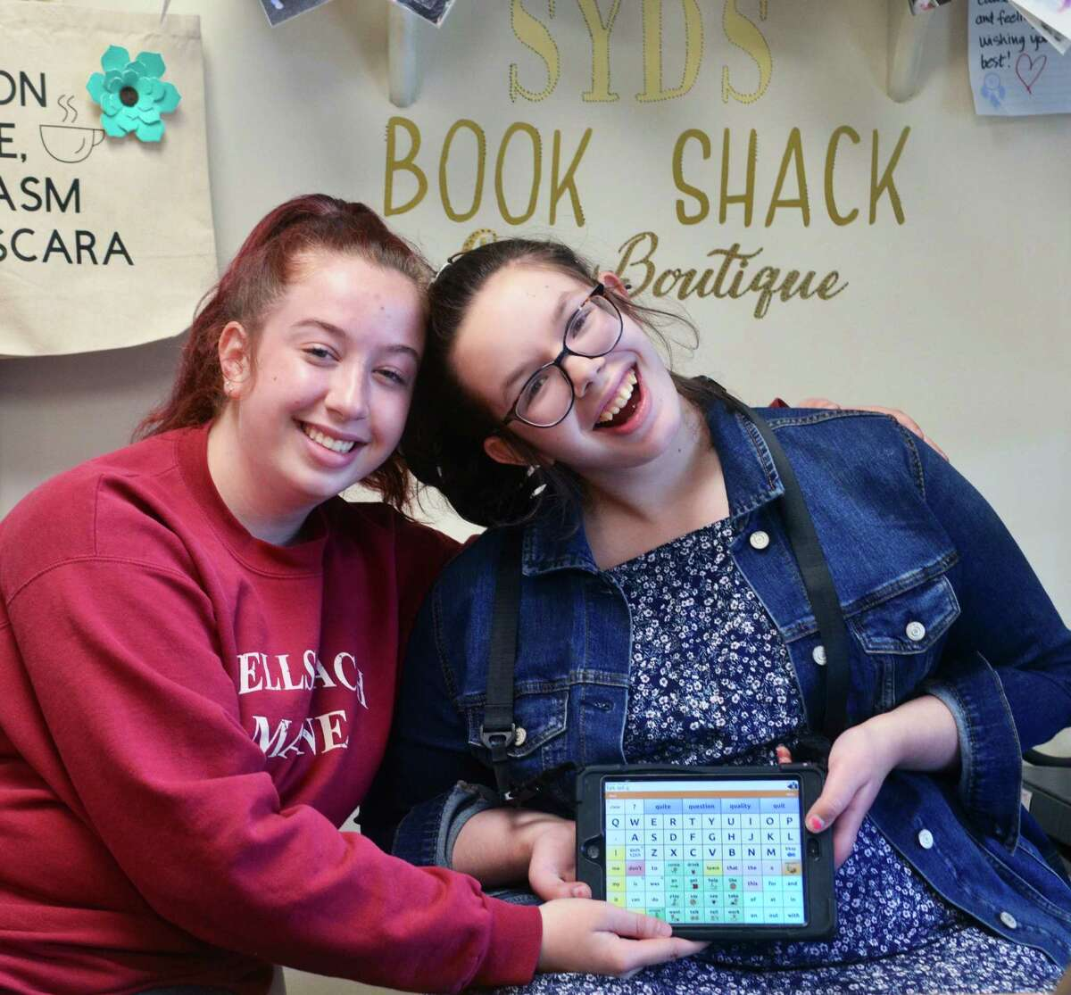 Syd Daggett, a 16-year-old who is on the autism spectrum and is nonverbal, right, with her twin sister, twin sister, Maddie, who volunteers at the bookstore.