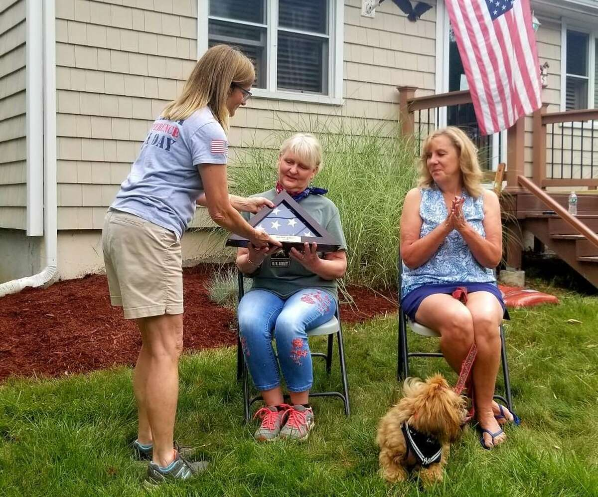 Carol May of House of Heroes Connecticut presents an American flag box to Robbin Wyatt Ford as Ford's friend Lisa Pavlich-Kuhn looks on.