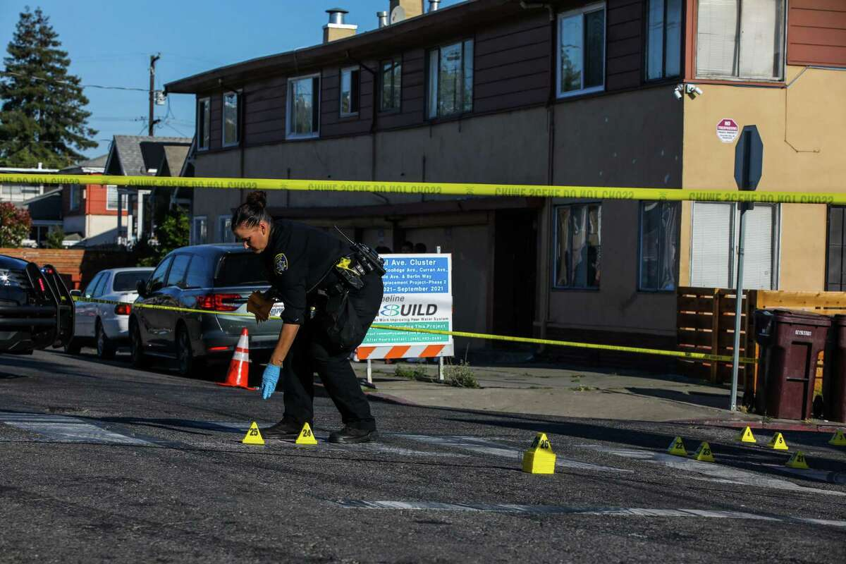 Oakland police Officer A. Goodard works a crime scene at School St. and Pleitner Ave. following a shooting on Friday, June 25, 2021, in Oakland, Calif. Oakland is shifting some money from the police budget over to violence prevention and other services.