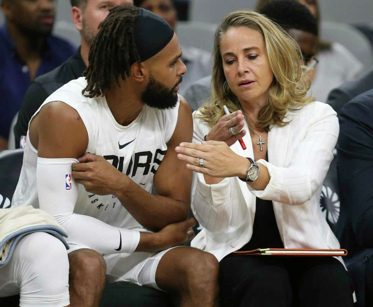 San Antonio Spurs assistant coach Becky Hammon talks with Patty Mills on the bench during the first half against the Miami Heat at the AT&T Center, Sunday, Sept. 30, 2018.