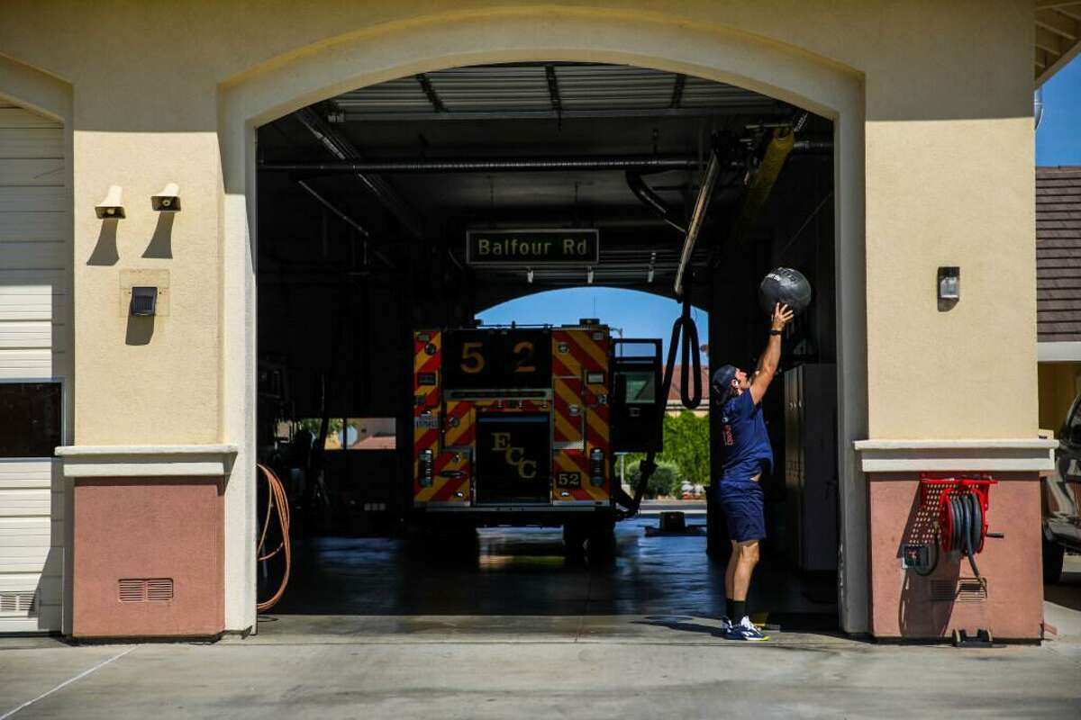 Jared Gavard, 31, of Orangevale (Sacramento County) exercises outside at the East Contra Costa Fire Protection District's Station 52 on June 17 in Brentwood. The fire department averages about 10 calls a day, 350 calls a month and 3,000 calls a year.
