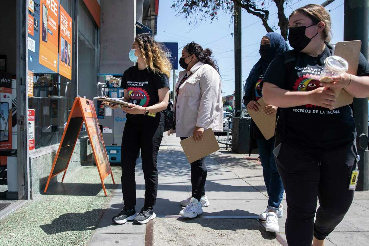 Katherine Flores, Sehar Fatima, Amira Amana and Nicole Menegus, from left, walk door-to-door down Mission Street with vaccine information, as part of a partnership between San Francisco's Department of Public Health and UCSF.