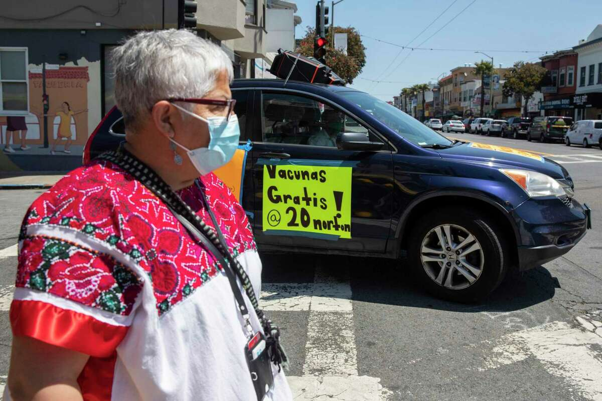 Neighborhood vaccine lead Bertha Hernandez's husband drives the mobile vaccine outreach car down Mission Street from a community pop-up vaccine site in partnership with San Francisco's Department of Public Health and UCSF in the Excelsior district of San Francisco on June 18, 2021.