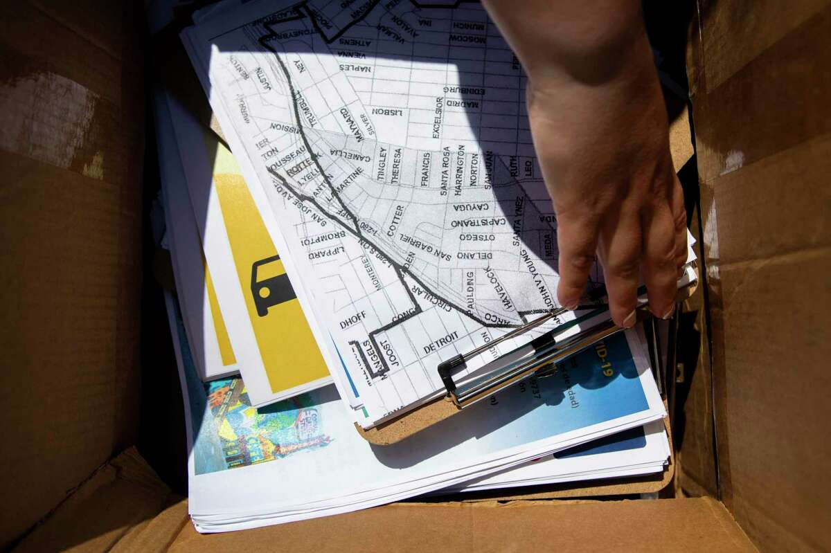 Nicole Menegus grabs a map of low-vaccinated areas as she prepares for neighborhood outreach at a community pop-up vaccine site in the Excelsior district of San Francisco in partnership with San Francisco's Department of Public Health and UCSF on June 18, 2021.
