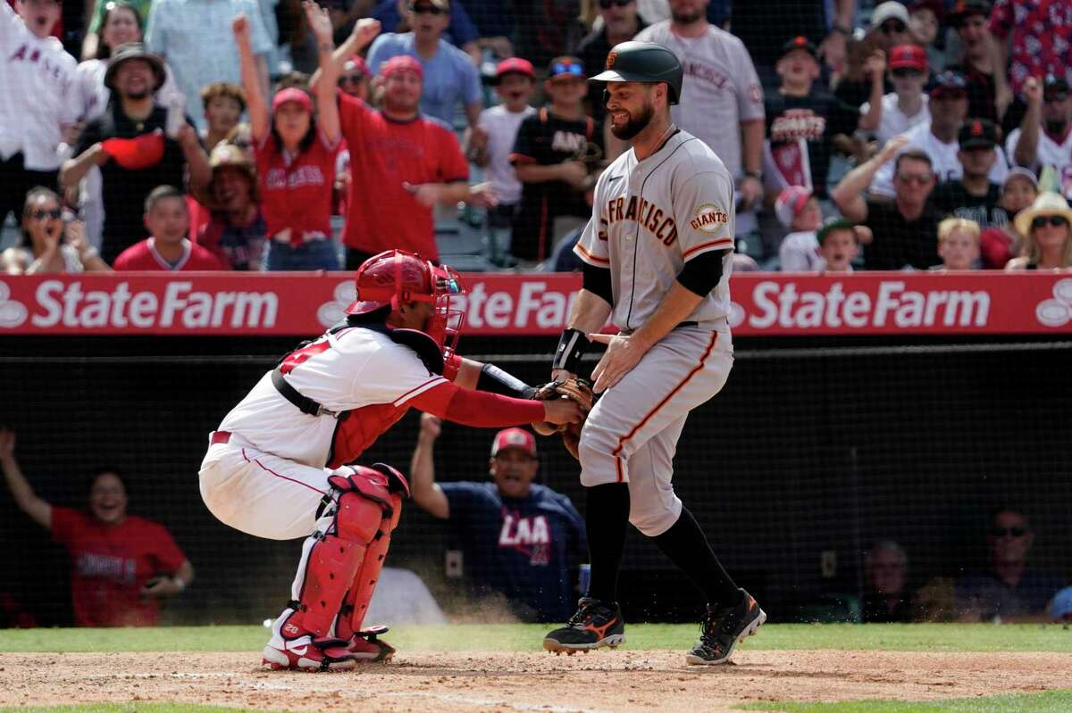 San Francisco Giants' Brandon Belt, right, is tagged out at home by Los Angeles Angels catcher Kurt Suzuki as he tries to score on a runner's fielder's choice during the eighth inning of a baseball game Wednesday, June 23, 2021, in Anaheim, Calif. (AP Photo/Mark J. Terrill)
