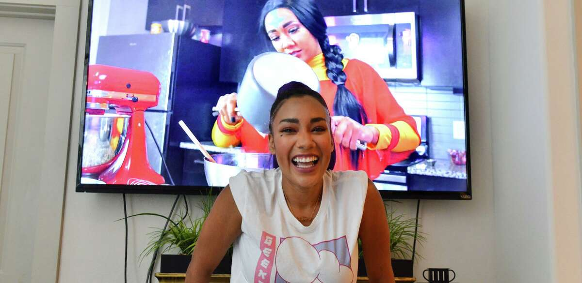 """San Antonio chef Mary Lou Davis stands in front of a TV displaying an episode of her YouTube show """"Geeks & Grubs"""" inspired by """"Avatar: The Last Airbender."""""""