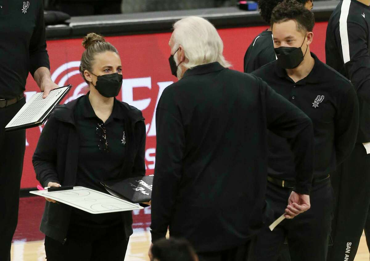 Assistant coach Becky Hammon and Spurs head coach Gregg Popovich gather during a timeout in the game against the Atlanta Hawks at the AT&T Center on Thursday, April 1, 2021.