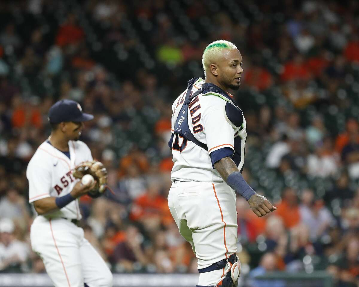 Houston Astros catcher Martin Maldonado (15) sports bleach blonde hair with a green stripe after he took his head gear off to catch Baltimore Orioles Pedro Severino's pop out during the sixth inning of an MLB baseball game at Minute Maid Park, Monday, June 28, 2021, in Houston.