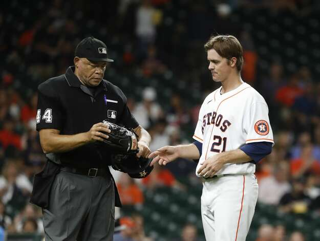 Houston Astros starting pitcher Zack Greinke's hat and glove are inspected by home plate umpire Kerwin Danley after the fifth inning of an MLB baseball game at Minute Maid Park, Monday, June 28, 2021, in Houston. Photo: Karen Warren/Staff Photographer / @2021 Houston Chronicle