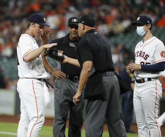 Home plate umpire Kerwin Danley checks Houston Astros starting pitcher Zack Greinke's hat and glove for foreign substances after Baltimore Orioles Ryan Mountcastle ground out to end the top of the first inning of an MLB baseball game at Minute Maid Park, Monday, June 28, 2021, in Houston. Photo: Karen Warren/Staff Photographer / @2021 Houston Chronicle