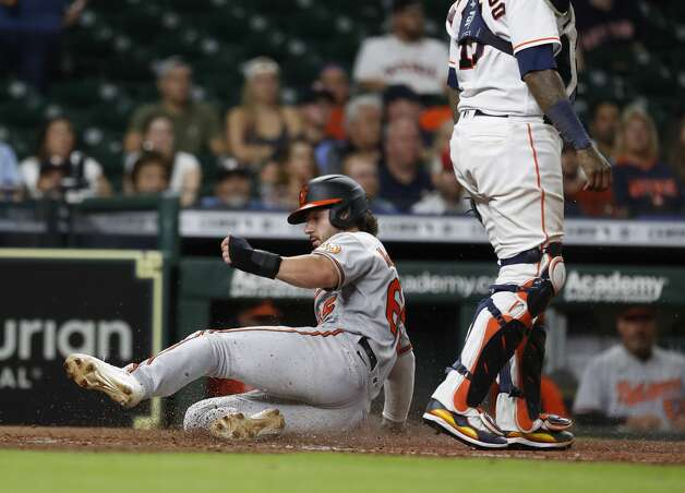 Baltimore Orioles Ryan McKenna (65) slides home as he scored on Pedro Severino's RBI double off of Houston Astros relief pitcher Brandon Bielak during the ninth inning of an MLB baseball game at Minute Maid Park, Monday, June 28, 2021, in Houston. Photo: Karen Warren/Staff Photographer / @2021 Houston Chronicle