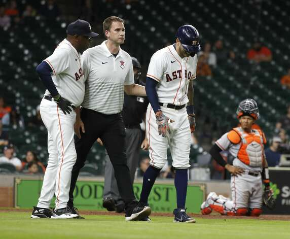 Houston Astros Carlos Correa (1) is tended to by trainer Jeremiah Randall after getting hit by a pitch from Baltimore Orioles relief pitcher Paul Fry during the ninth inning of an MLB baseball game at Minute Maid Park, Monday, June 28, 2021, in Houston. Photo: Karen Warren/Staff Photographer / @2021 Houston Chronicle