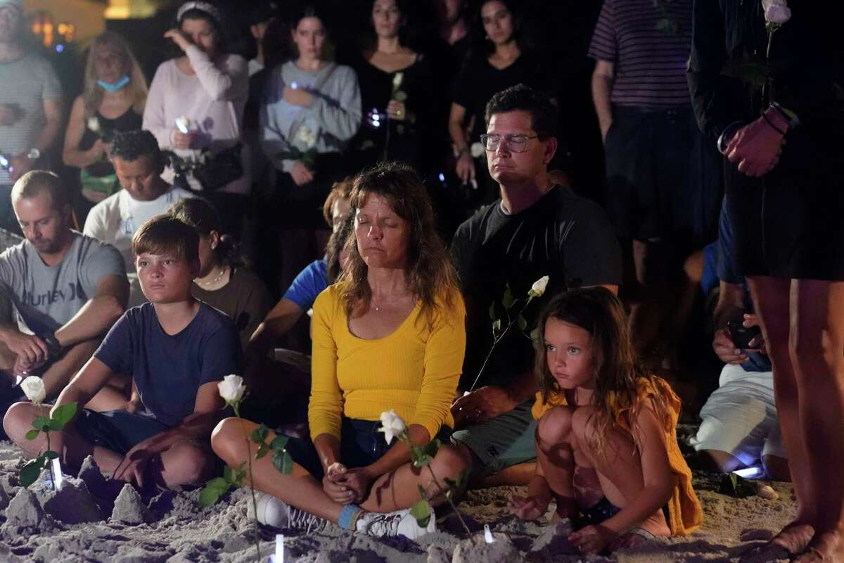 People gather at a vigil, late Monday, June 28, 2021, in Surfside, Fla. The vigil remembered those that died, are missing and those injured after a residential building collapsed last Thursday.