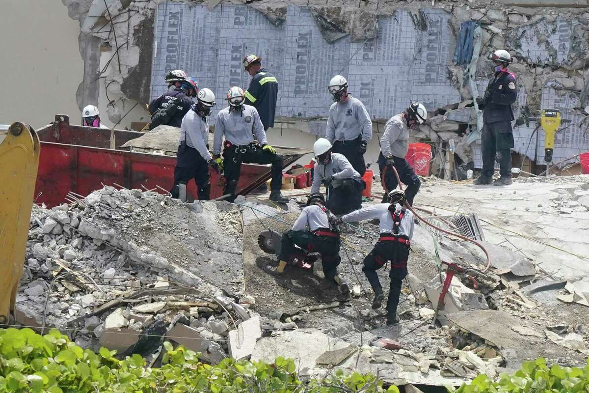 Workers cut a large slab of concrete at the Champlain Towers South condo, Monday, June 28, 2021, in Surfside, Fla. Many people were still unaccounted for after Thursday's fatal collapse.