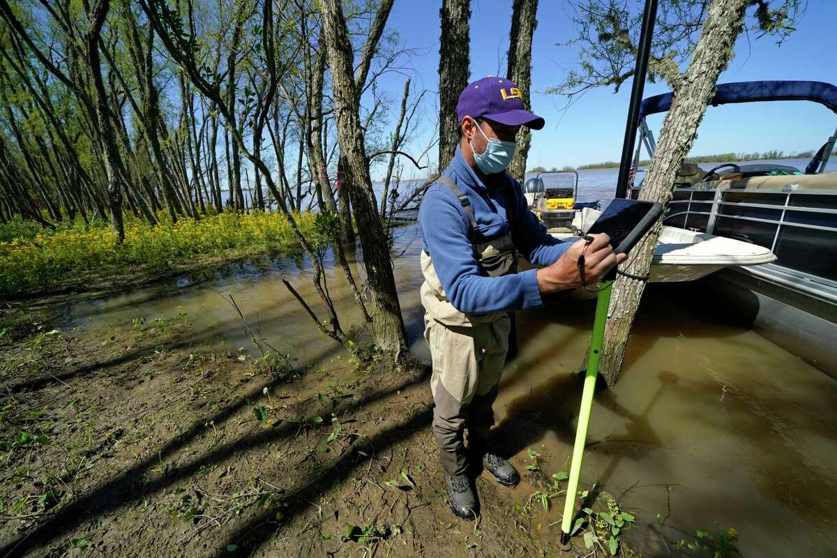 Andre Rabay, research scientist for the LSU Department of Oceanography and Coastal Science uses a real time kinetic (RTK) GPS to take measurements on Mike Island, part of the Wax Lake Delta in the Atchafalaya Basin, in St. Mary Parish, La., Friday, April 2, 2021. NASA is using high-tech airborne systems along with boats and mud-slogging work on islands for a $15 million study of these two parts of Louisiana's river delta system.