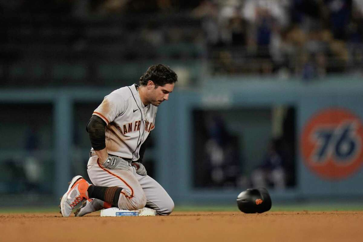 San Francisco Giants' Mike Tauchman kneels on second base after he was tagged out by Los Angeles Dodgers' Chris Taylor while trying to take the base on a single during the ninth inning of a baseball game, Monday, June 28, 2021, in Los Angeles. (AP Photo/Jae C. Hong)