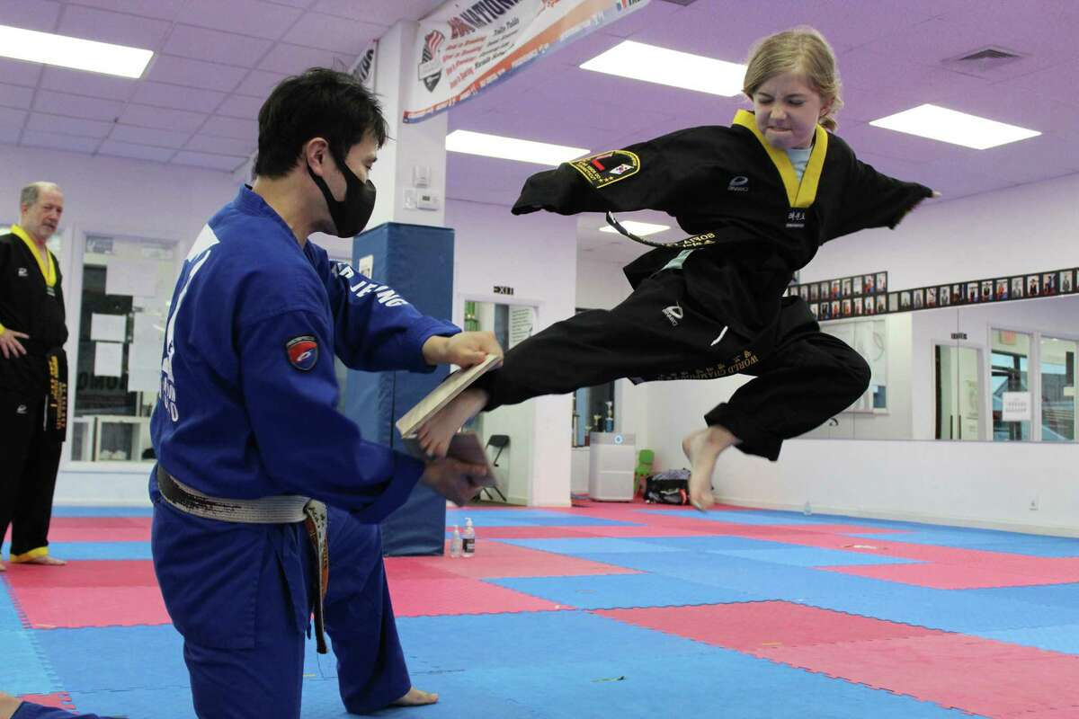Ten-year-old Sofia Cluney snaps a wooden board after flying through mid-air at the World Champion Taekwondo dojo in Ridgefield. She was assisted by master Wooyeol Jeong as her father, Stephen, looked on. The Cluneys are the first in the dojo's history to have four black belts within their family.