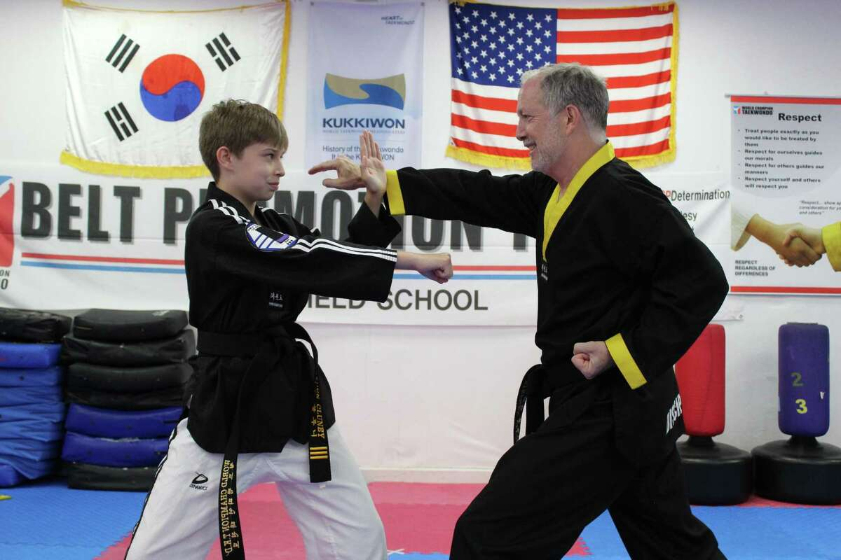 Fourteen-year-old Hayden Cluney prepares to spar with his father, Stephen, at the World Champion Taekwondo dojo in Ridgefield. The Cluneys are the first in the dojo's history to have four black belts within their family.