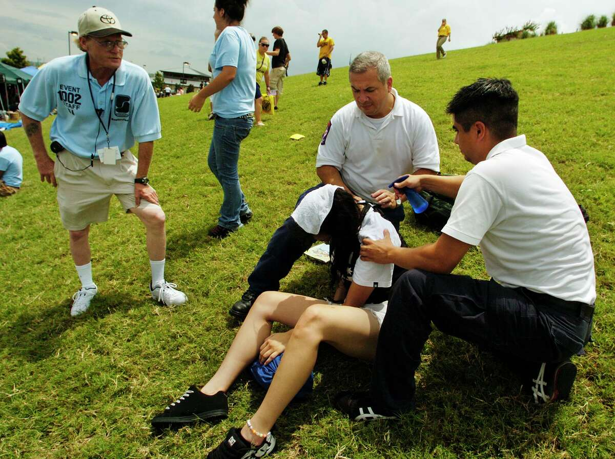 An unidentified concert attendant suffers from heat exhaustion and is helped by paramedics at a concert in San Antonio.