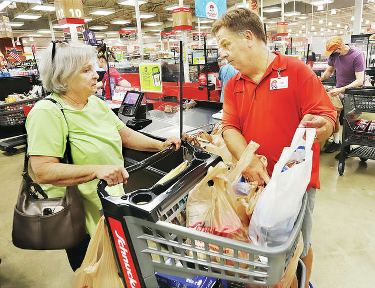 Edwardsville Schnucks employee Bill Tucker, right, shows Jan McKey, left, of Holiday Shores, the white reusable plastic bag the store was handing out in response to a new plastic bag fee coming to establishments throughout the city beginning Monday, July 12.