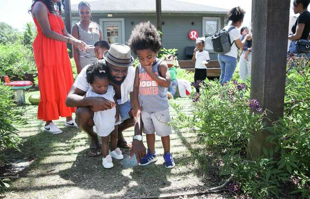 """Andre Evans, center, and his children Chancellor, 3, right, and Addison, 1, left, look at a worm as they play in a watermelon patch set up by Ivy Leaf Farms on Sunday, June 13, 2021, at the Heights Mercantile Farmer's Market in Houston. """"I'm a budding gardener,"""" Andre Evans said. """"Hopefully, one day I'll have a booth,"""" he said as his wife laughed. Photo: Jon Shapley, Houston Chronicle / Staff Photographer / © 2021 Houston Chronicle"""