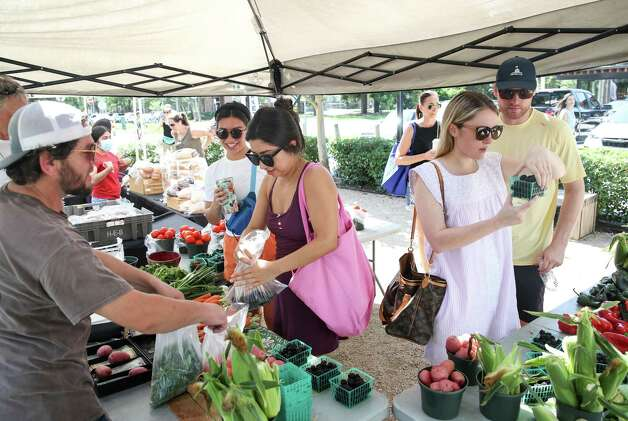 Lizzie Villareal, center, and her sister Kat Villareal, center-left, shop for produce at a booth from Wood Duck Farm on Sunday, June 13, 2021, at the Heights Mercantile Farmer's Market in Houston. The farm is located in San Jacinto County. Photo: Jon Shapley, Houston Chronicle / Staff Photographer / © 2021 Houston Chronicle